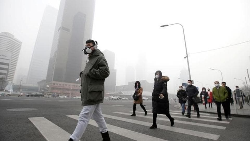 File photo of a man wearing a respiratory protection mask walks toward an office building during the smog after a red alert was issued for heavy air pollution in the Chinese capital, Beijing.