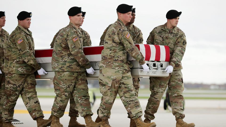 A US Army cary team carries the flag-draped transfer case containing the remains of a soldier at Dover Air Force Base November 8, 2017 in Dover, Delaware.