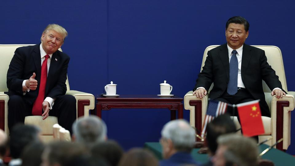 US President Donald Trump gestures to his delegation next to and Chinese President Xi Jinping during a business event at the Great Hall of the People in Beijing on November 9.