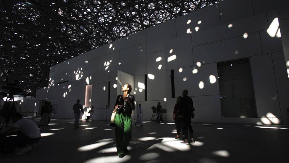 A journalist walks under light filtering through the dome at the Louvre Abu Dhabi. France's Pritzker prize-winning architect Jean Nouvel, conjures up the image of an Arab medina with a silver-toned dome and honeycombed patterns which appear to float over the white galleries. To reach the ground, each ray of light crosses eight layers of perforations, creating a constantly shifting pattern that mimics the shadows cast by palm trees or the roof of a traditional Arab market. (Kamran Jebreili / AP)