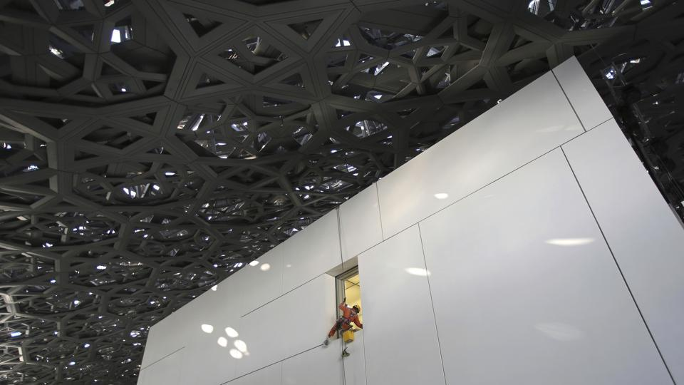 A worker cleans a window under the dome of the Louvre Abu Dhabi. During construction, the project faced criticism over labourer work conditions, including low pay and long hours in the heat. Multiple deaths were reported, according to Abu Dhabi authorities. Hundreds working on projects on the island, including the Louvre, were deported or lost work visas for launching strikes, according to a 2015 Human Rights Watch report. (Kamran Jebreili / AP)