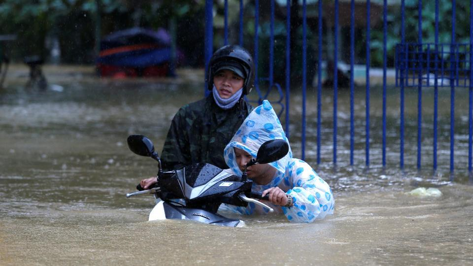 A woman pushes a motorbike along a flooded street in Hoi An after the typhoon hit.  Typhoon Damrey, the year's 12th major storm, struck on Saturday, leaving 25 missing and 197 injured, the country's search and rescue committee said. (Kham / REUTERS)