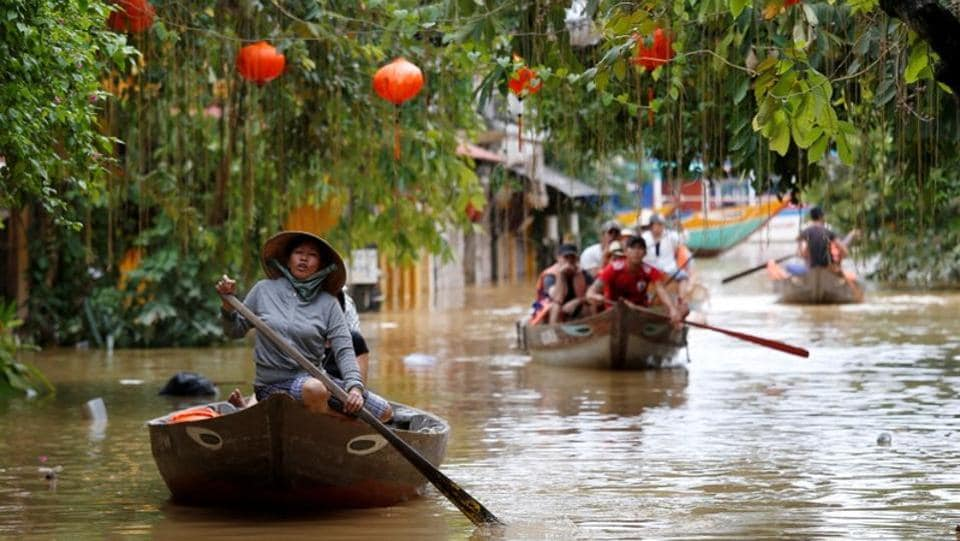 People ride in boats as they pass the houses flooded by the typhoon. The typhoon caused extensive damage ahead of APEC summit that is attended by leaders from around the world, although those meetings that started yesterday in the central city of Danang were not affected. (Kham / REUTERS)