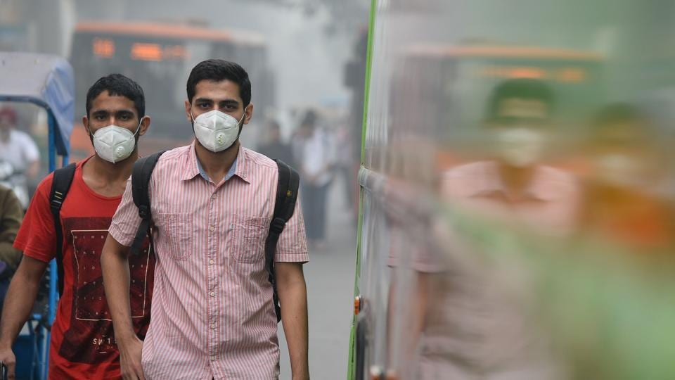 Commuters wear masks as they walk along a road amid heavy smog in New Delhi on Thursday.