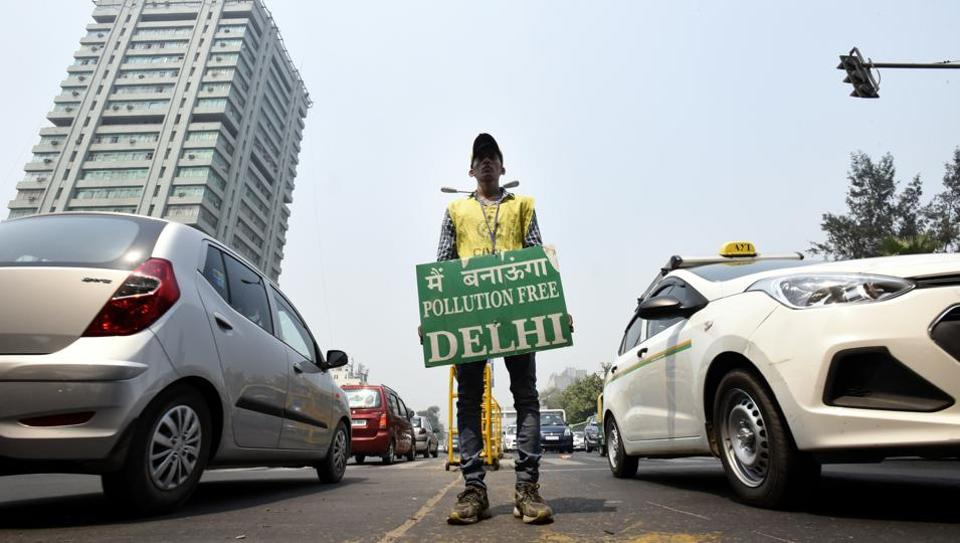 A volunteer holds a placard displaying a message against pollution in New Delhi during the second phase of the odd-even campaign on April 30, 2016.