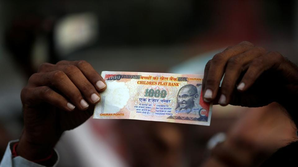 A demonstrator shows an old fake Rs 1000 note during a protest organised by the Congress party to mark a year since demonetisation, in Ahmedabad on November 8, 2017.