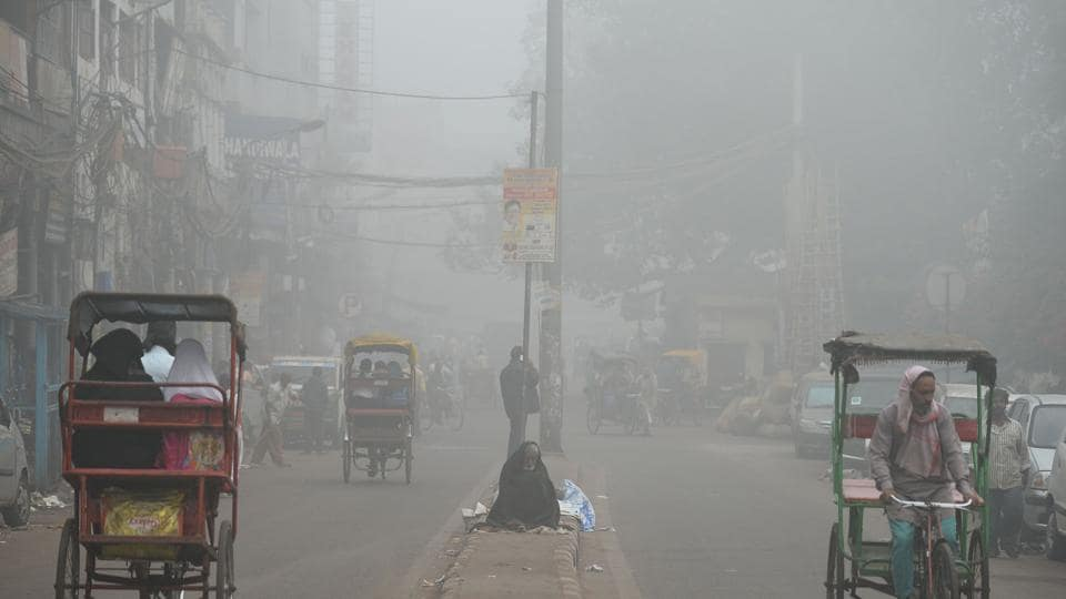A homeless man sits on a road median amid heavy smog in New Delhi on November 8, 2017.