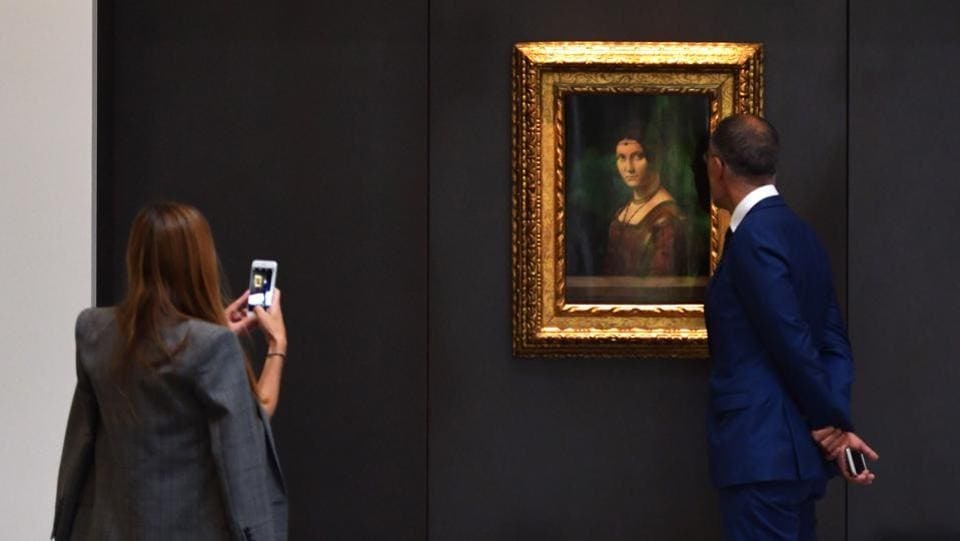 "Visitors look at a painting titled ""La Belle Ferroniere"" by Leonardo Da Vinci at the Louvre Abu Dhabi. It also has around 300 pieces on loan, including an 1887 self-portrait by Vincent van Gogh and Da Vinci's painting pictured above. (Guiseppe Cacace / AFP)"