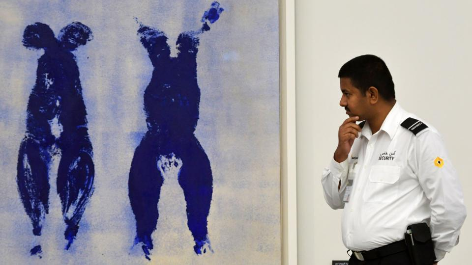 "A security guard looks at ""Untitled Anthropometry Ant 110"" by artist Yves Klein at the Louvre Abu Dhabi Museum. The authorities have put in place strict measures to protect the art from the heat in a country where summer temperatures soar well above 40 degrees Celsius. (Guiseppe Cacace / AFP)"