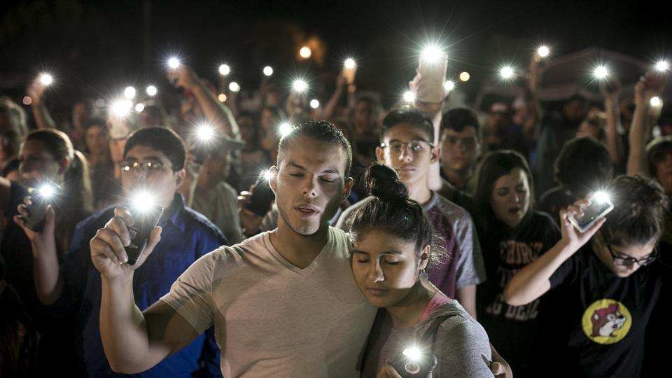 Matthew Mata and Erika Gonzalez participate in a memorial service for the victims of Sunday's church shooting in Sutherland Springs, Texas on November 6, 2017. The gunman of the deadly shooting had a history of domestic violence and sent threatening text messages to his mother-in-law, a member of First Baptist, before the attack in which he fired at least 450 rounds at helpless worshippers, authorities said Monday. (Jay Janner / Austin American-Statesman via AP)