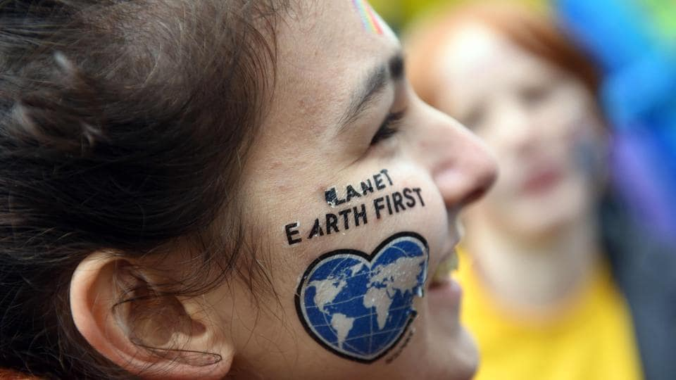 "A female protester wears the slogan --Planet Earth First-- on her face, at a Greenpeace demonstration under the motto ""Kids for Earth"" in Bonn on November 6, 2017. The 23rd UN Climate Conference (COP23) is the first such gathering since President Donald Trump announced he would extricate the US from the 2015 Paris Agreement aimed at curbing global warming. (Henning Kaiser / AFP)"