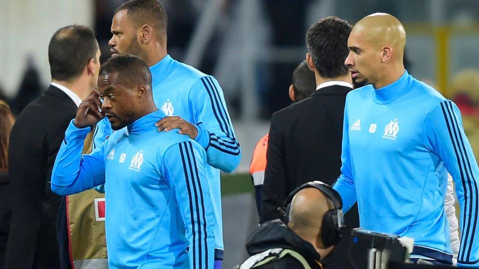 Patrice Evra (L) is escorted off the pitch by teammates Rolando and Doria (R) after an argument with Marseille supporters.