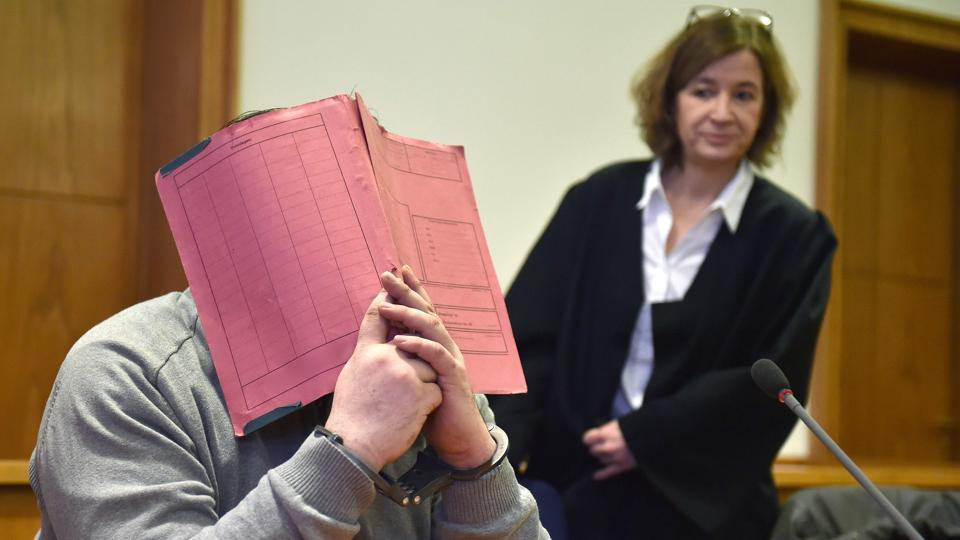 German former male nurse Niels Hoegel hiding his face behind a folder as he waits next to his lawyer Ulrike Baumann (R) for the opening of another session of his trial at court in Oldenburg, northwestern Germany on February 26, 2015.