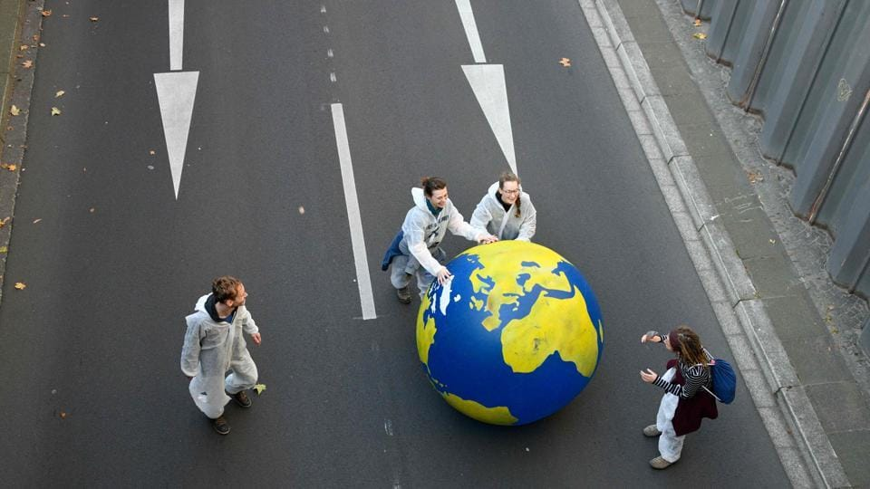 Demonstrators roll a giant globe through a street as they take part in a so-called Climate March against fossil-based energy like coal in Bonn, western Germany.