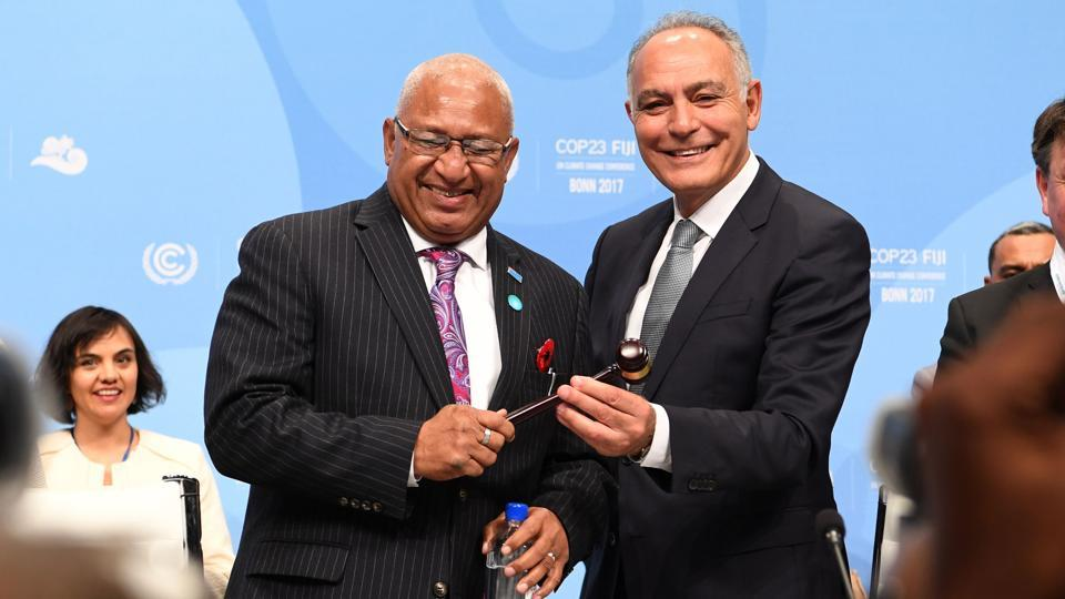 Salaheddine Mezouar (R), Moroccan Foreign Minister and President of COP22, hands over a symbolic hammer to Frank Bainimarama, Prime Minister of Fiji and President of the COP23, during the opening session. Following a cascade of grim reports on the gathering pace of global warming, Fiji's Prime Minister made an open plea to the world for 'urgent action' on climate change.  (Patrik Stollarz / AFP)