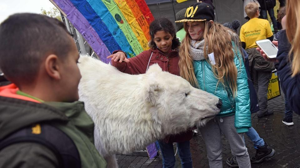 "Children caress a mock polar bear at a demonstration under the motto ""Kids for Earth"" in Bonn during the COP23 United Nations Climate Change Conference on November 6, 2017. According to the organisers, this year's conference, from November 6 to 19, 2017, is where ""nations of the world will meet to advance the aims and ambitions of the Paris Agreement and achieve progress on its implementation guidelines"". (Henning Kaiser / AFP)"
