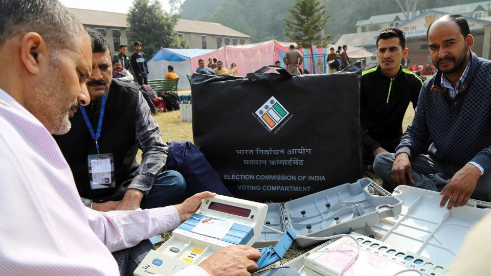 An election official checks an EVM before leave for the polling station at Mandi on Tuesday.