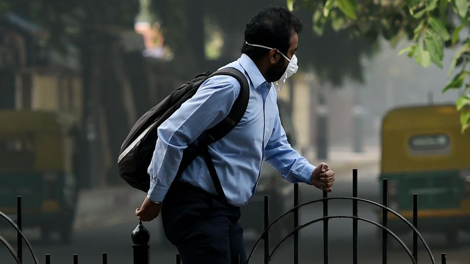 A man wears a mask to protect himself from pollution as he crosses a divider on a road in New Delhi, November 9. Many residents have rushed to buy protective masks to combat the toxic menace.