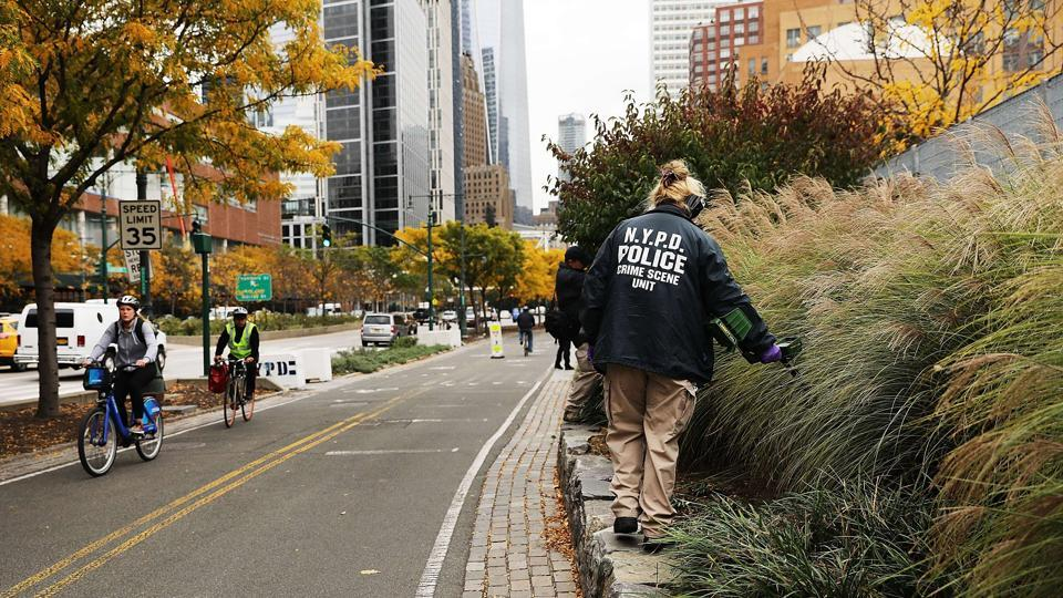 A member of the police department's crime scene unit searches the location where terrorist Sayfullo Saipov drove down a Manhattan bike path and went on a rampage with a truck in New York City. Eight people were killed and 12 were injured when 29-year-old Saipov intentionally drove a truck onto a bike path