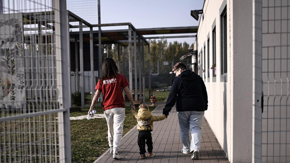 An educator (L) holds the hand of a child outside the Biobab  nursery at Bollate Penitentiary. Opened as part of facilities to improve the wellbeing of staff, the creche was initially little used with prison employees reluctant to switch from their established childcare arrangements. Opening it up to the public brought an unexpectedly enthusiastic response from the prison's neighbours. (Marco Bertorello / AFP)