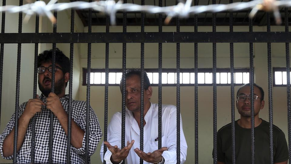 Aung Naing Soe, left, Burmese freelance journalist and interpreter, Hla Tin, Burmese driver, and Lau Hon Meng, Singaporean journalist stand for their first court appearance after being accused for allegedly flying drones illegally over parliament buildings Friday, Nov. 10, 2017, in Naypyitaw, Myanmar.
