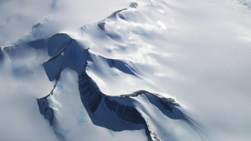 Mountain's peek through land ice seen from NASA's Operation IceBridge research aircraft in the Antarctic Peninsula region on October 31, 2017, above Antarctica. Operation IceBridge has been studying how polar ice has evolved over the past eight years and is currently flying a set of nine-hour research flights over West Antarctica to monitor ice loss aboard a retrofitted 1966 Lockheed P-3 aircraft. (Mario Tama / Getty Images / AFP)