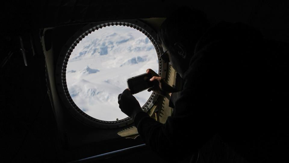 Operation IceBridge project scientist Nathan Kurtz takes photographs from high above in the Antarctic Peninsula region, on November 3, 2017. These flights will provide a yearly, multi-instrument look at the behaviour of the rapidly changing features of the Greenland and Antarctic ice. (Mario Tama / Getty Images / AFP)