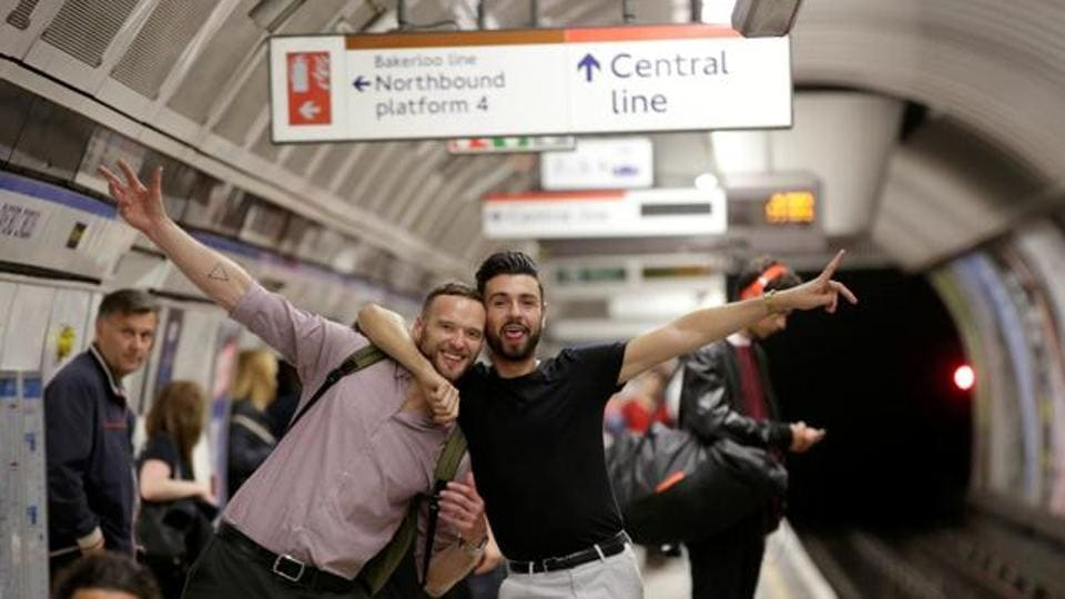 Passengers pose for a photograph as they wait for the Night Tube train service at Oxford Circus on the London underground system.