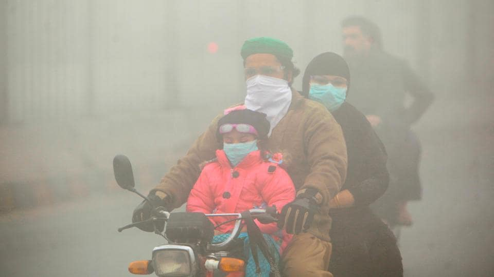 People use face masks to protect themselves from morning smog as they ride on bike along a road in Lahore on Friday.