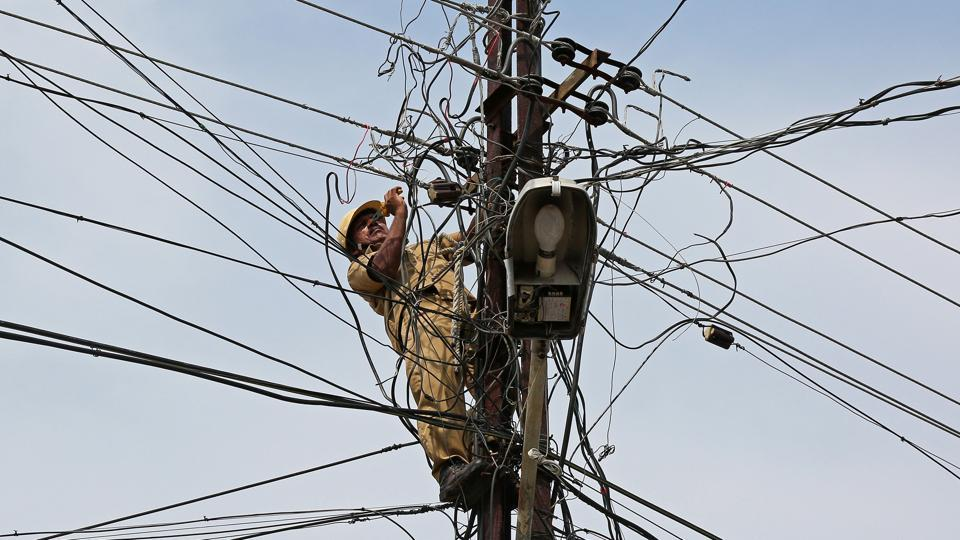 A worker repairs tangled power lines on a electric pole in Kochi. (Sivaram V / REUTERS)