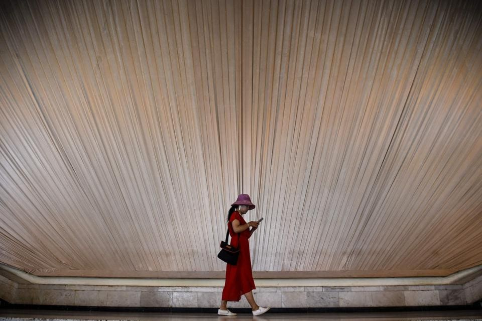 A woman looks at her phone as she walks inside an exhibition centre in Shanghai on September 8.