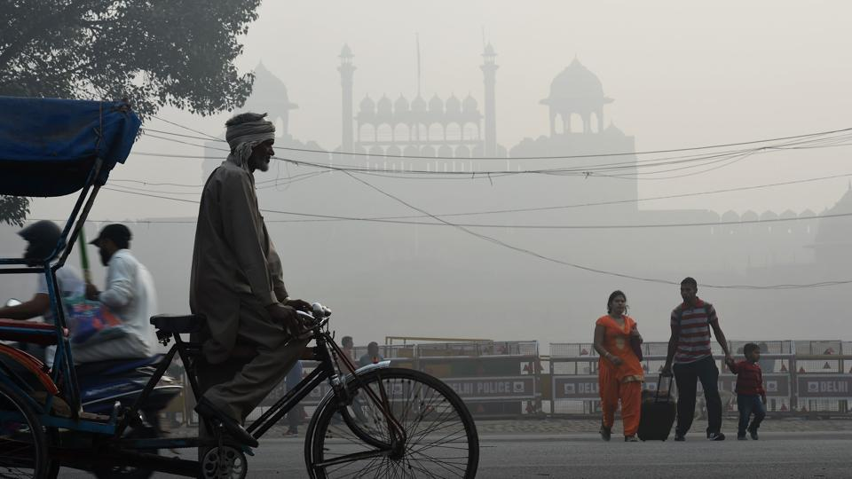 An Indian family crosses a road amid heavy smog in front of the Red Fort in New Delhi on November 10, 2017. Large swathes of India's northern states remained under dense smog that has shut hundreds of thousands of schools, disrupted air and railway services and forced residents to stay indoors.