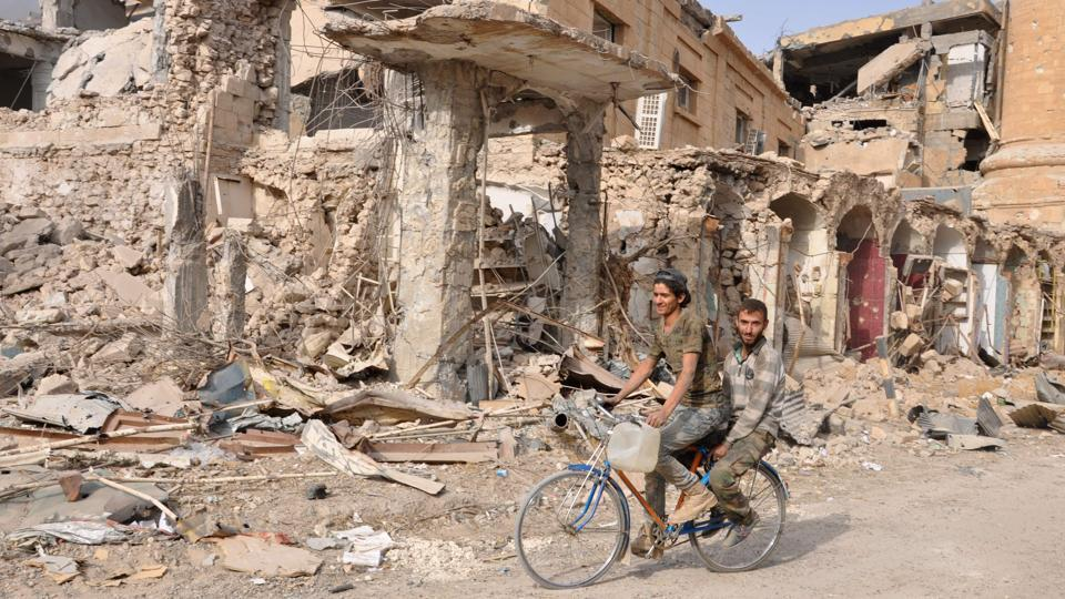 Men ride a bicycle in the eastern Syrian city of Deir Ezzor during a military operation by government forces against the Islamic State (IS) on November 4, 2017. On November 3, Russian-backed Syrian regime forces took full control of Deir Ezzor, which was the last city where IS still had a presence after being expelled from Hawija and Raqa last month. (Stringer / AFP)