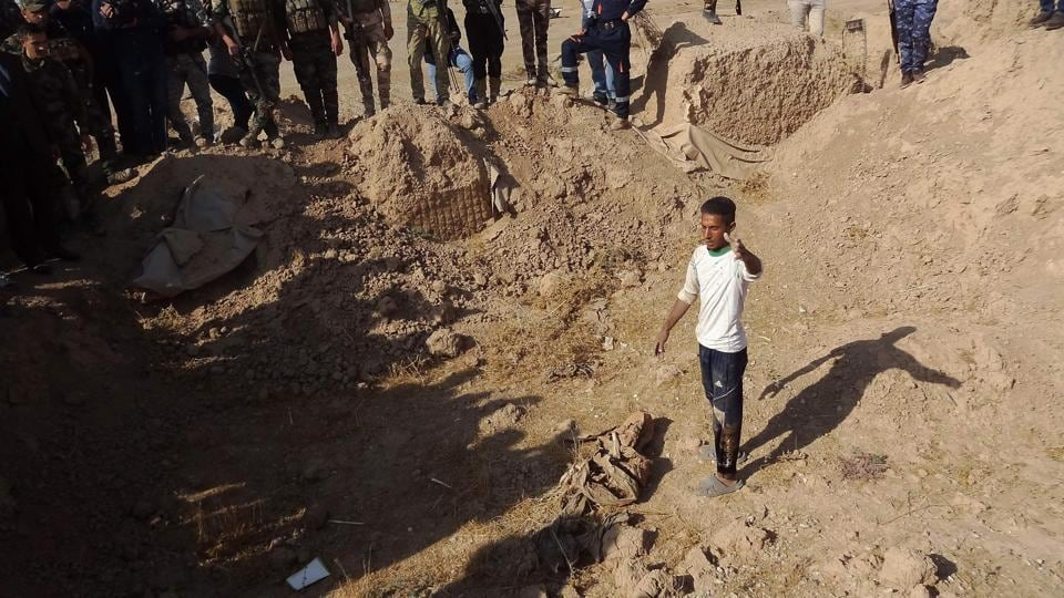 Iraqi forces search the site of a suspected mass grave containing the remains of victims of the Islamic State group, near the former al bakara military base, south west of Hawija on November 11.