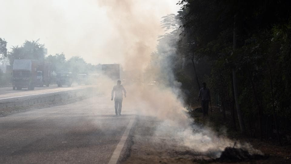 Apart from stubble burning and pollution from vehicular traffic, waste and dry leaves have also heightened the smog crisis in Delhi- NCR. One such scene can be seen here on the NH-8 at the Dharuhera border in New Delhi.  (Ravi Choudhary / HT Photo)