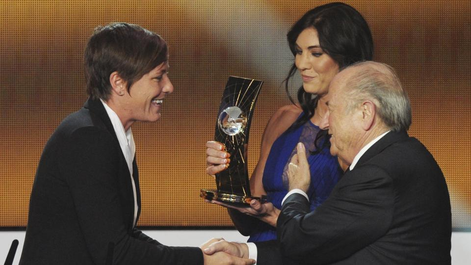 Abby Wambach(L) of the United States is presented the FIFA Women's World Player of the Year award by Hope Solo(C)and then FIFA President Sepp Blatter(R)during the FIFA Ballon d'Or Gala held in Zurich in 2013.