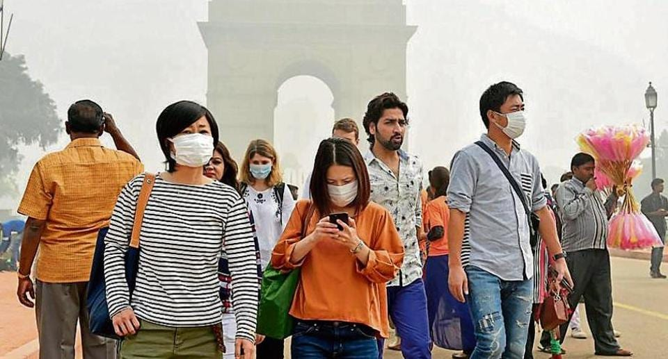 People wear protective masks at Rajpath as pollution level remained severe in the Capital on Sunday.