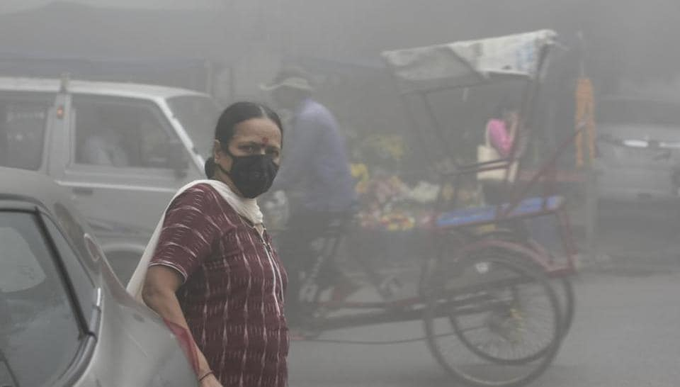 A woman wears a face mask in Mayur Vihar as New Delhi continues to reel under poor air quality  and low visibility.