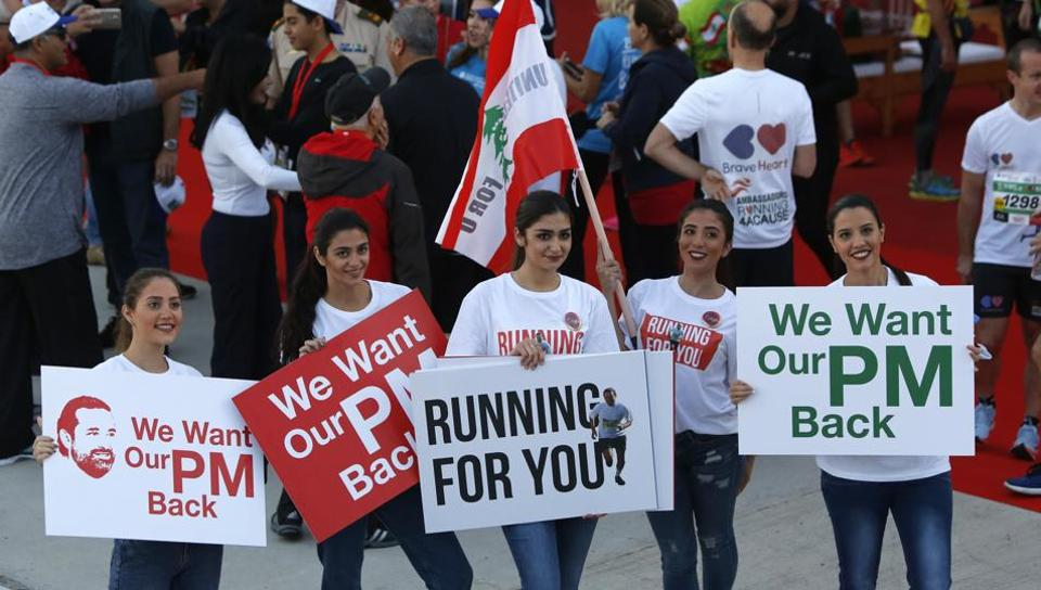 Lebanese women hold placards supporting the outgoing Lebanese Prime Minister Saad Hariri to return from Saudi Arabia during the Beirut Marathon in Beirut, Lebanon, Sunday.