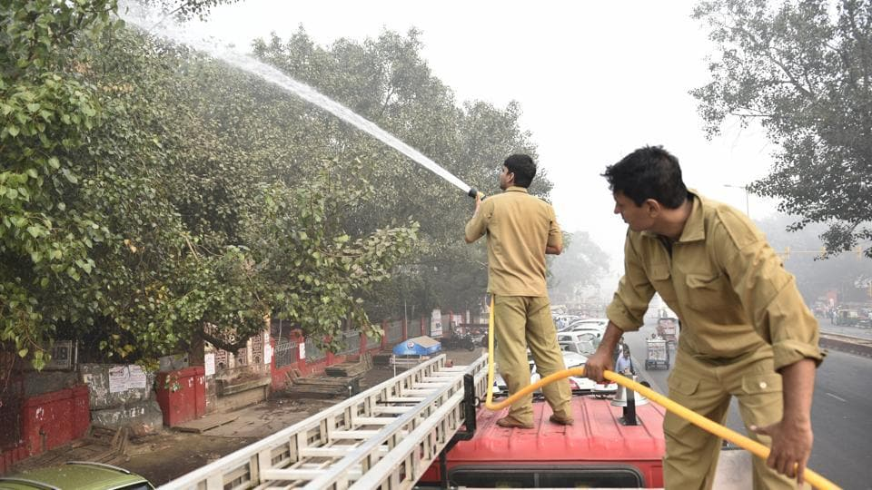 Delhi Fire Services personnel sprinkle water on trees to settle dust: one of the several measures taken to control severe air pollution in the city.