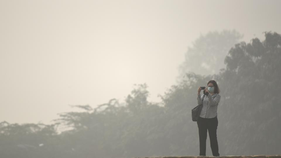 A tourist at Qutub Minar wears a mask as a thick blanket of haze engulfs New Delhi on Sunday.