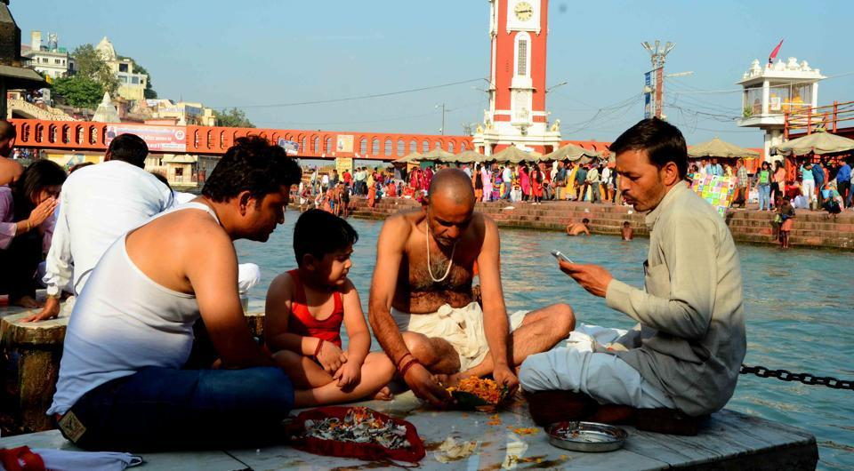 A family performs ash immersion rituals at Subash Ghat,which is being objected to by Ganga Sabha.