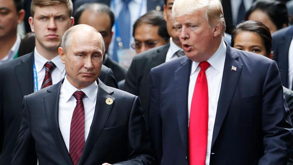 US President Donald Trump and Russia's President Vladimir Putin talk as they make their way to take the