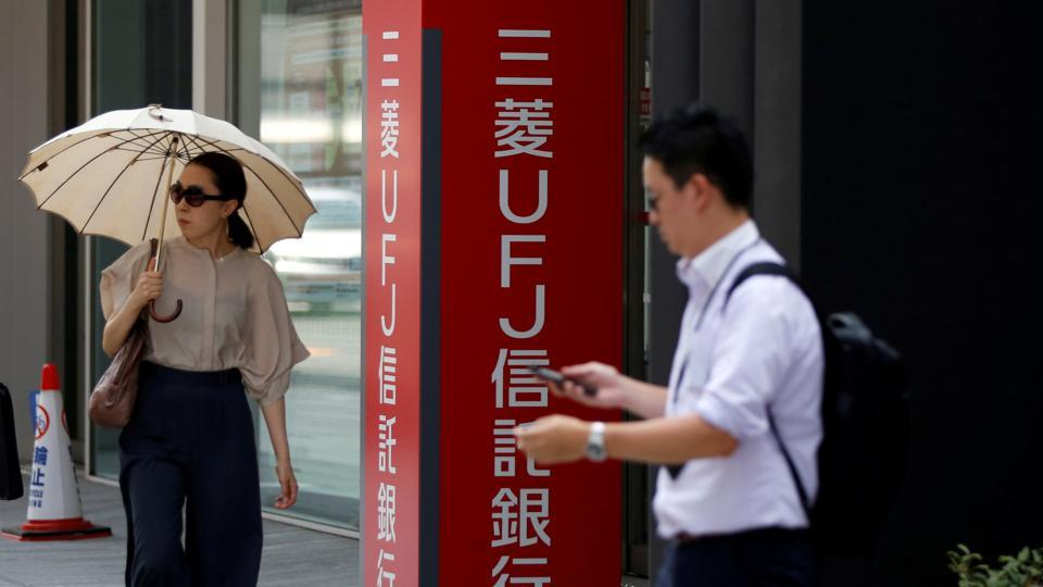 Passersby walk past sign boards  in Tokyo, Japan July 31, 2017.
