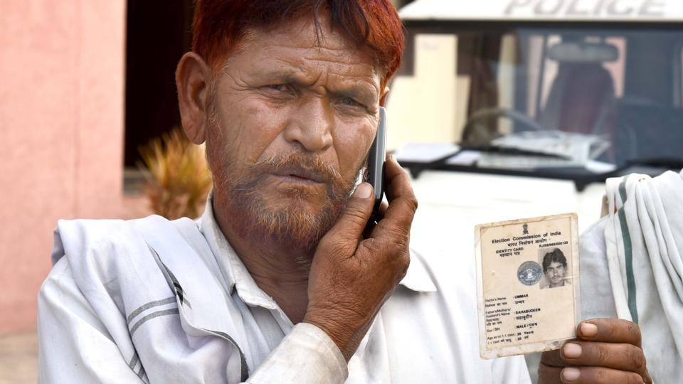 Ilyas Khan, uncle of the victim Ummar Mohammed, holds his IDcard.