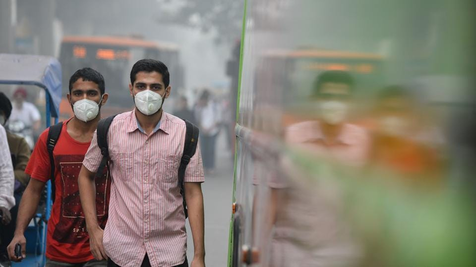 People wear masks as they walk along a road amid heavy smog in New Delhi on November 9, 2017. The poor air quality triggered several emergency measures in India's national capital.