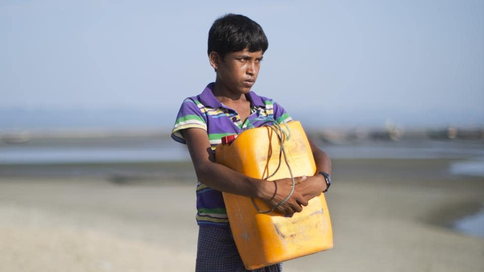In this Nov. 4, 2017, photo, Rohingya Muslim Nabi Hussain, 13, poses for a portrait with the yellow plastic drum he used as a flotation device while crossing the Naf river in Shar Porir Dwip, south Cox's Bazar, Bangladesh. )