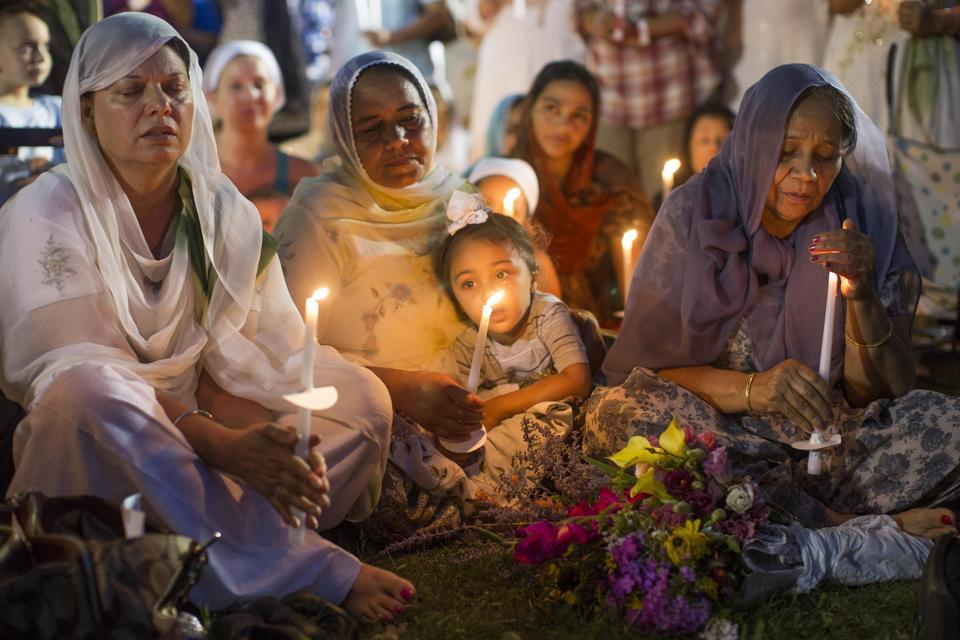People attend a candle light vigil at the Oak Creek Civic Center on August 7, 2012, two days after a gunman shot to death six Sikhs at a gurdwara in Oak Creek, Wisconsin.