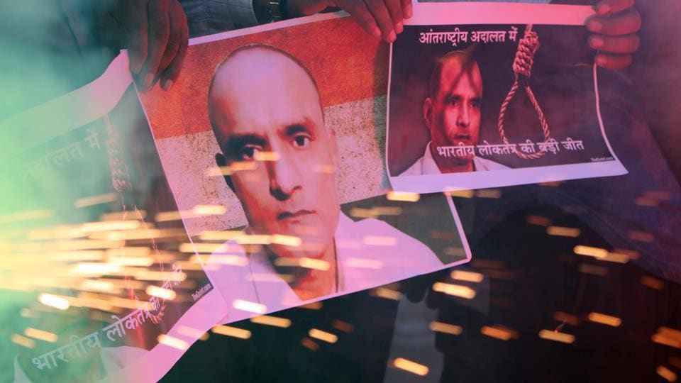 People hold posters of Indian naval officer Kulbhushan Jadhav as they celebrate the International Court of Justice staying the execution of Jadhav, in Ahmadabad, in May 2017.