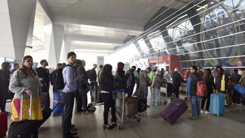 Passengers wait at the entrance of the T3 terminal of the Indira Gandhi International Airport  in New Delhi.